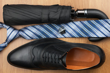 Classic mens shoes, tie, umbrella,cufflinks on the wooden floor