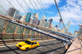New York taxi crossing Brooklyn Bridge and Manhattan skyline