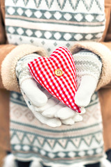 Girl hands in white knitted mittens holding romantic red heart
