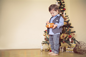 Boy opening present in front of christmas tree