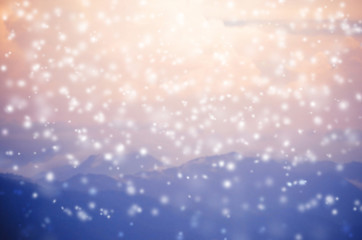 blurred background of snow falling on blue mountain and pink sky