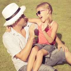 father and daughter playing on the grass at the day time