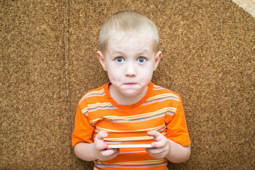 Surprised boy holding a smartphone in the hands and sitting on