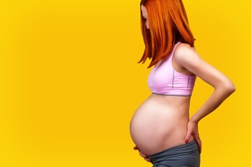 Standing red hair pregnant woman, isolated on yellow background.