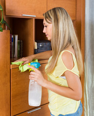 girl cleaning furniture with cleanser and rag