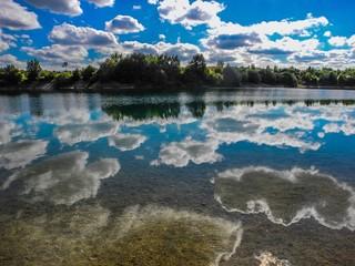 Schäfchenwolken spiegeln sich im Baggersee