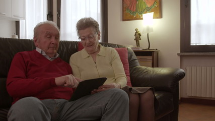 Elder senior couple browsing and watching videos on a tablet