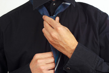 Guy tying his tie over black shirt close up