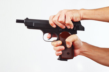 Hands reload gun on a white background