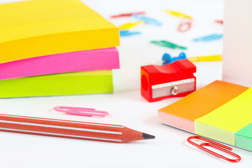Multicolored stationery supplies on white desktop close up