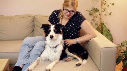Happy woman relaxing with a dog on the sofa at home.