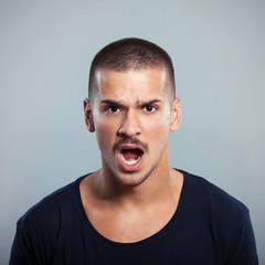 Portrait of a young man shouting. Studio shot.