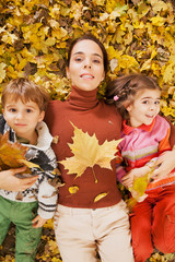 Family playing with autumn leaves in nature