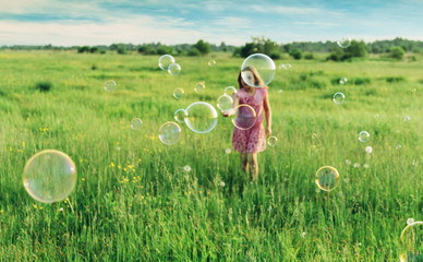 Cheerful girl playing among soap bubbles in summer