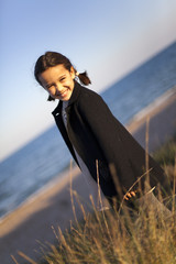 Niña con abrigo negro en la playa