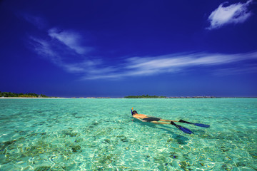 Young man snorkling in tropical lagoon with over water bungalows