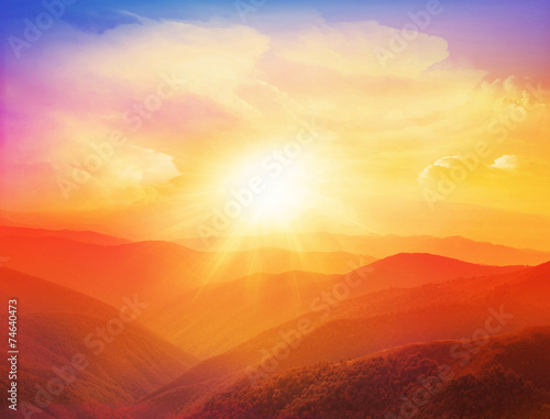 Majestic sunset in the mountains landscape with sunny beams. © Catwoman