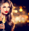 Sexy girl with glass of champagne over holiday background