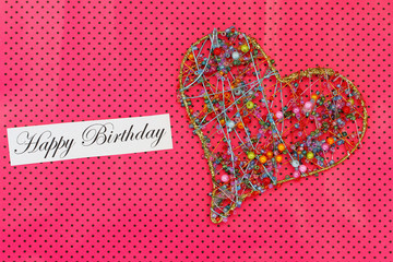 Happy Birthday card with heart made of colorful beads on pink