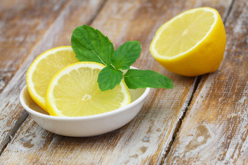 Lemon and mint leaves on rustic wooden surface