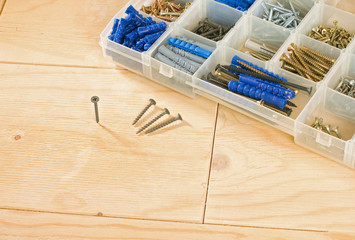 screws and toolbox on a wood background