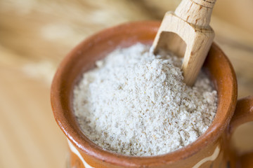 Flour with wheat in a clay bowl and shovel