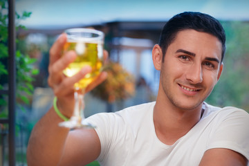 Young Man Rising a Glass in a Bar