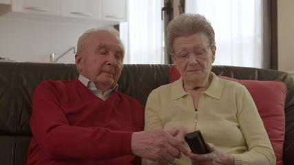 Elder couple arguing while watching TV and exchanging the remote