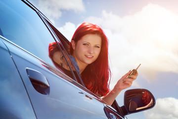 junge Frau hält Autoschlüssel aus dem Fenster
