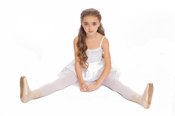 young girl in her dance clothes reaching down to touch her foot.