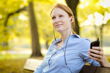 Young Woman Enjoying Music in a Park
