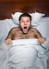 Surprised adult man  in bed