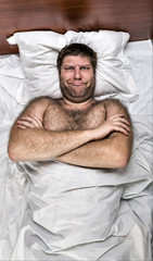 Unhappy man in bed with crossed hands