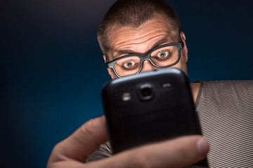 Man in glasses looks at his smartphone