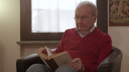 Elder man reading a book moves his eyeglasses to read better