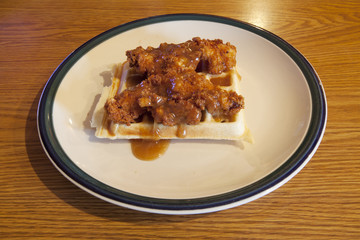 Chicken and waffle covered with a maple bourbon sauce