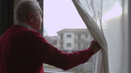 Worried elderly man moves the curtain and looks out the window