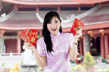 Asian woman holding red envelopes