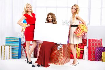 Three pretty women with empty board