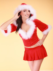 Portrait woman wearing santa claus costume on yellow