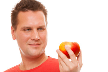 Happy man in red shirt holding apple. Diet health care healthy.