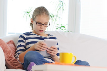 Girl with glasses having fun on tablet