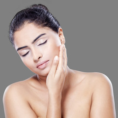 Beautiful woman touching her skin face
