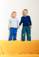 Happy childhood. Full length blond boys children on top of sofa