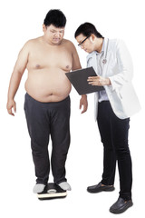 Doctor checking the weight of patient