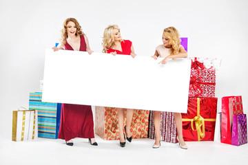Three attractive women holding empty board