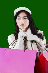 Girl holds shopping bags with green background