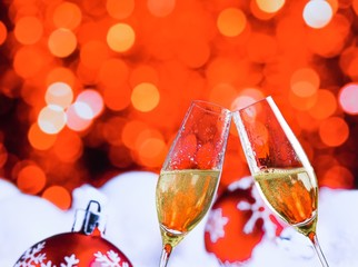 champagne flutes on red christmas bokeh decoration background