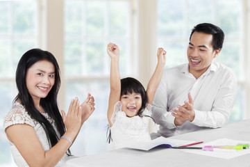 Joyful family finishing schoolwork together