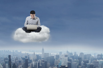 Man using laptop over cloud 1